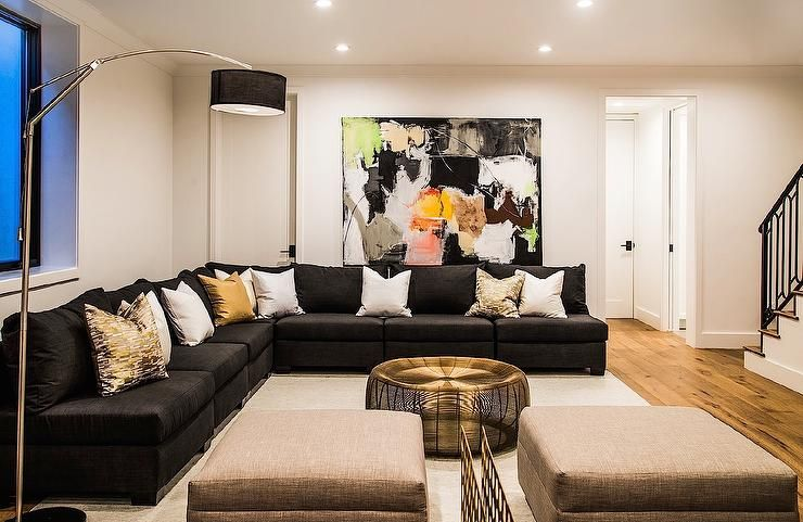 Chic family room features a black abstract art piece with splashes .