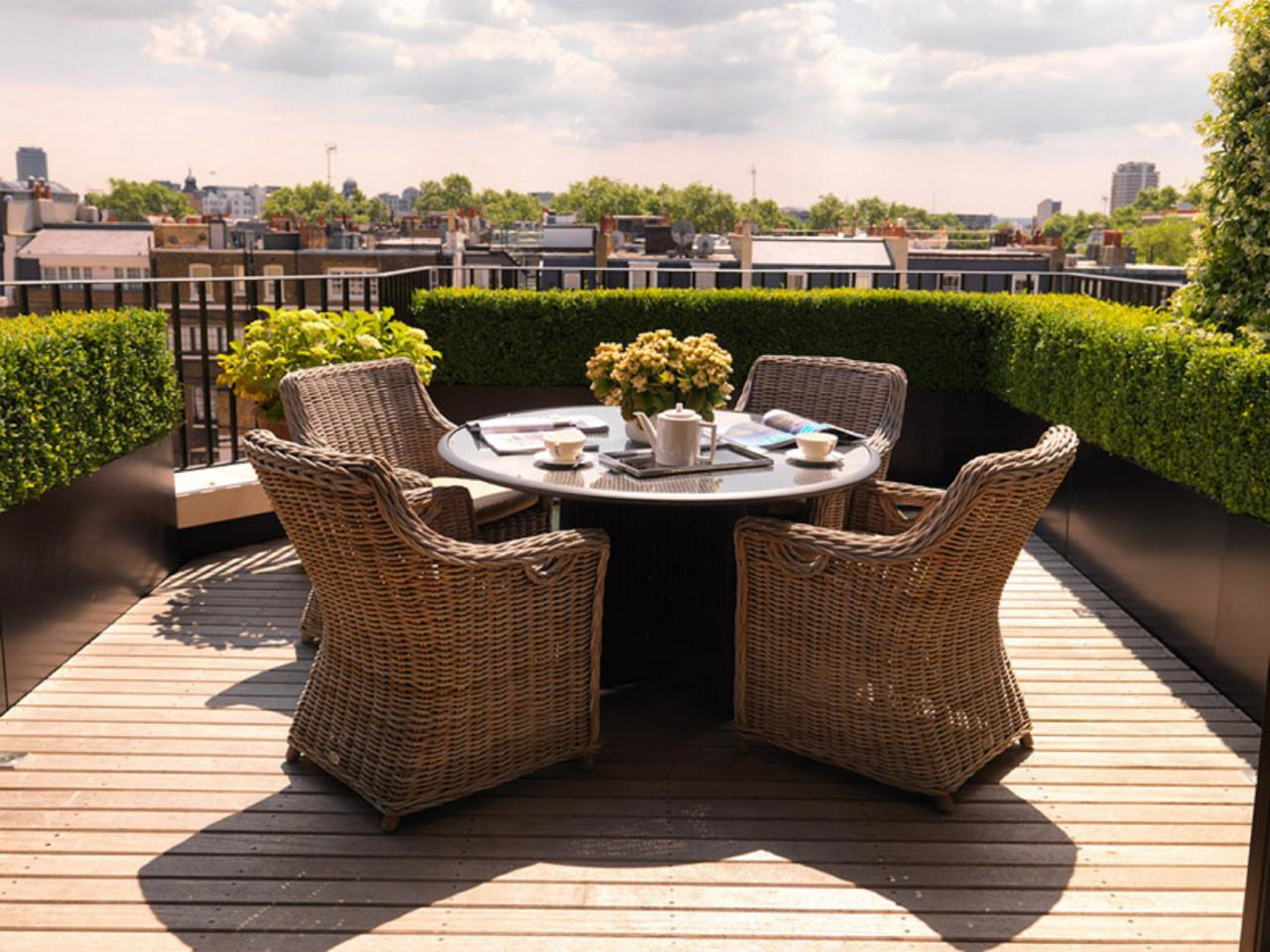Urban Dining Deck terrace furniture with privacy hedges and wicker chairs PQZMFFC