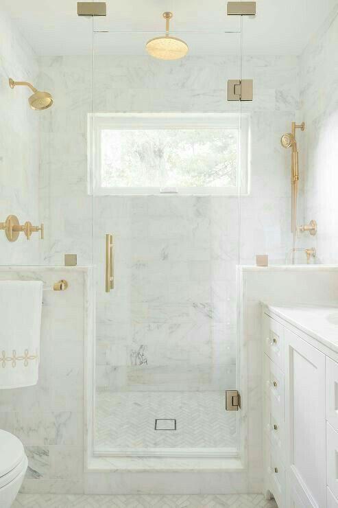 Gold and white bathroom.  Marble bathroom, rain shower head in gold.